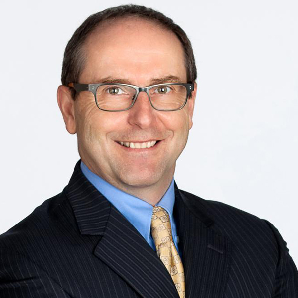 Bruce MacDonald in a suit, in front of white background.